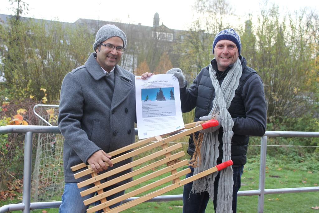 Zwei Männer halten Schlitten und Plakat.