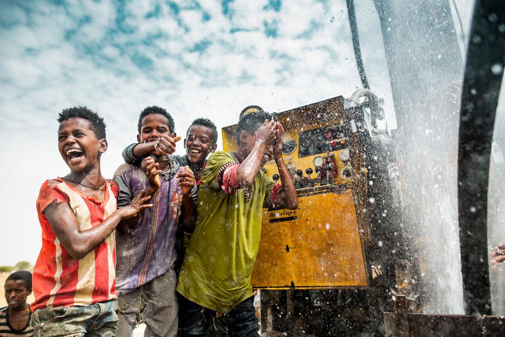 Kinder freuen sich über das Wasser