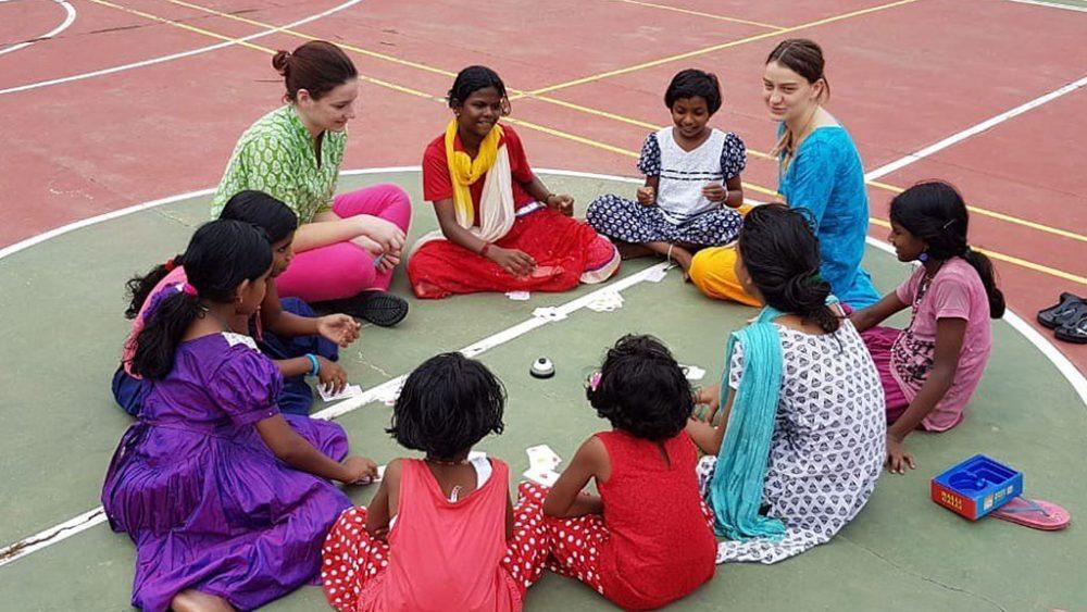 Kinder und Betreuerinnen sitzen im Kreis